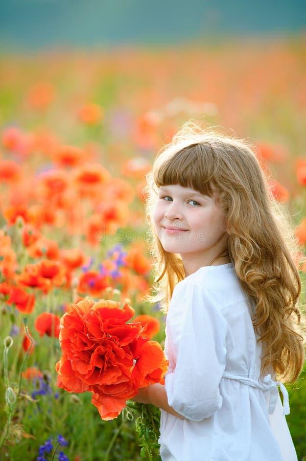 La chica joven que camina en el campo en el rojo florece en el summ soleado foto de archivo