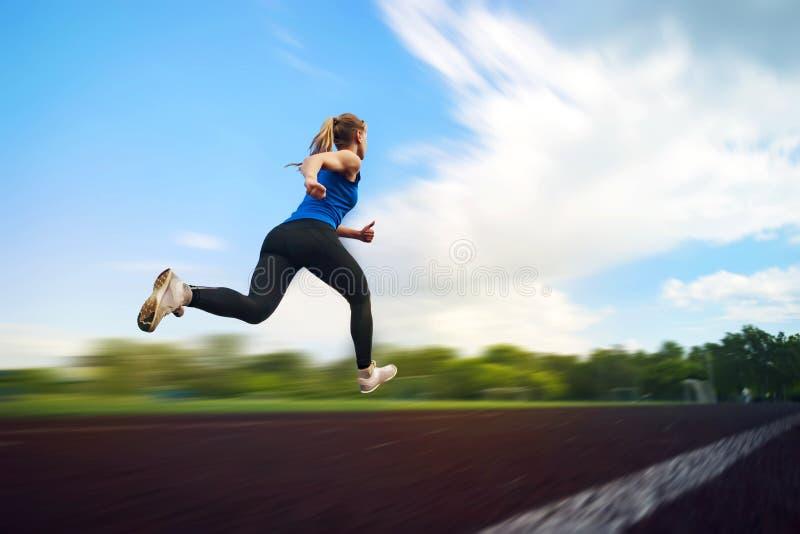 La chica joven que corre en el estadio, falta de definición en la mudanza Un atleta corre alrededor de la foto del salto de estad imagen de archivo libre de regalías