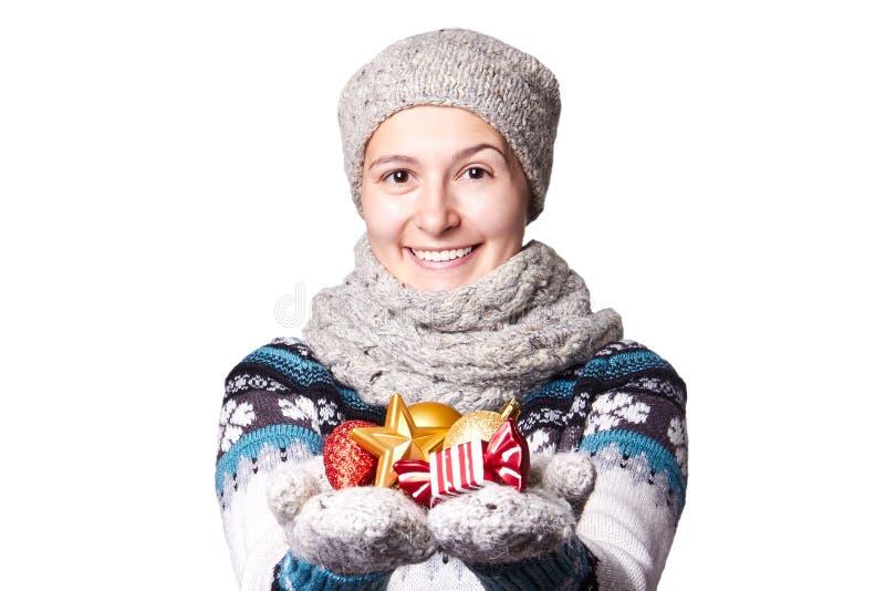 La chica joven que lleva a cabo una Navidad juega, las decoraciones Copyspace imagen de archivo libre de regalías