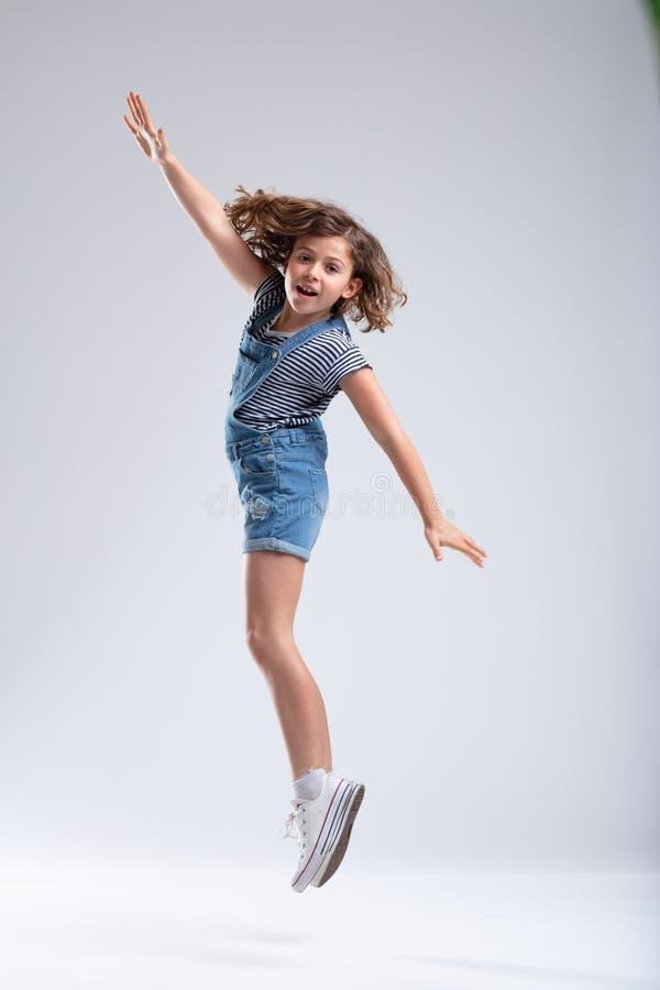 La chica joven que salta en el aire con los brazos extendidos imagen de archivo libre de regalías