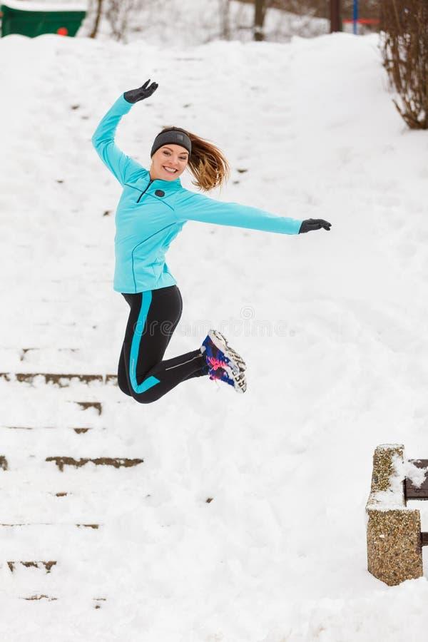 La chica joven que salta en la nieve fotos de archivo libres de regalías