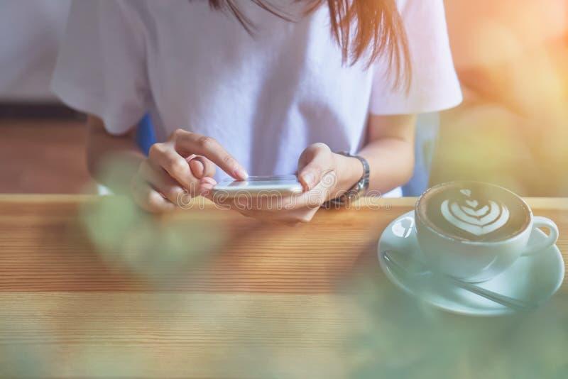 La chica joven que sostiene un teléfono blanco tiene una pantalla en blanco en café, y café en la tabla para hacer vida más relaj fotos de archivo