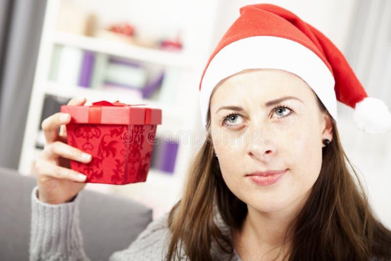 La chica joven quiere conjeturar el regalo de la Navidad fotografía de archivo