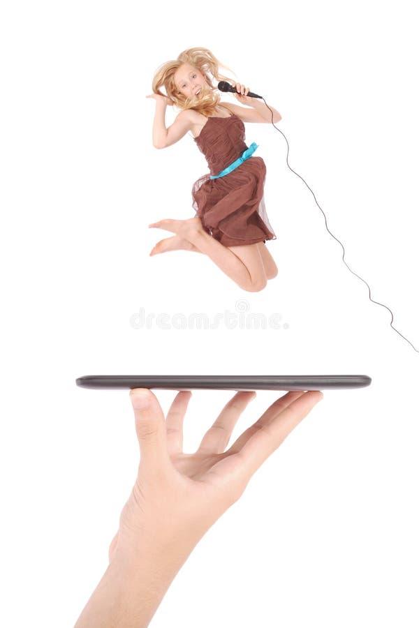 La chica joven salta y cantando con el micrófono usando la PC de la tableta en la mano de la gente imagen de archivo libre de regalías