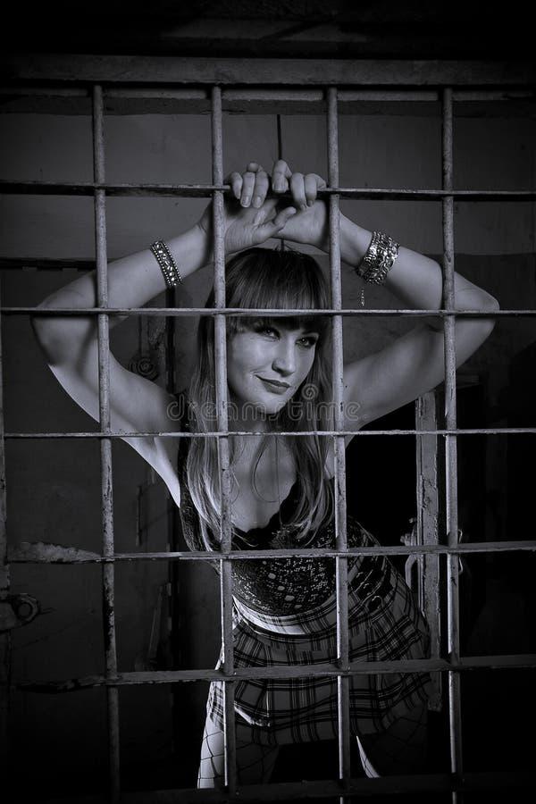 La chica joven se cerró detrás de las barras, rejilla, como en la prisión el parecer atractivo en falda corta fotos de archivo