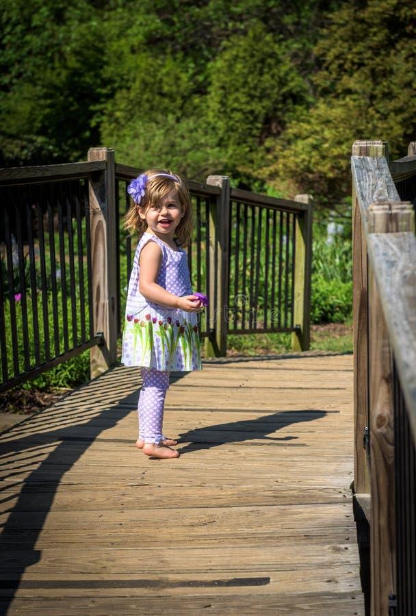 La chica joven se coloca en el puente en un jardín al aire libre fotos de archivo libres de regalías