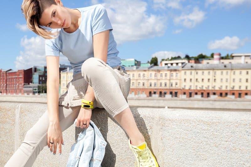 La chica joven se está sentando en el terraplén del río en ciudad imágenes de archivo libres de regalías