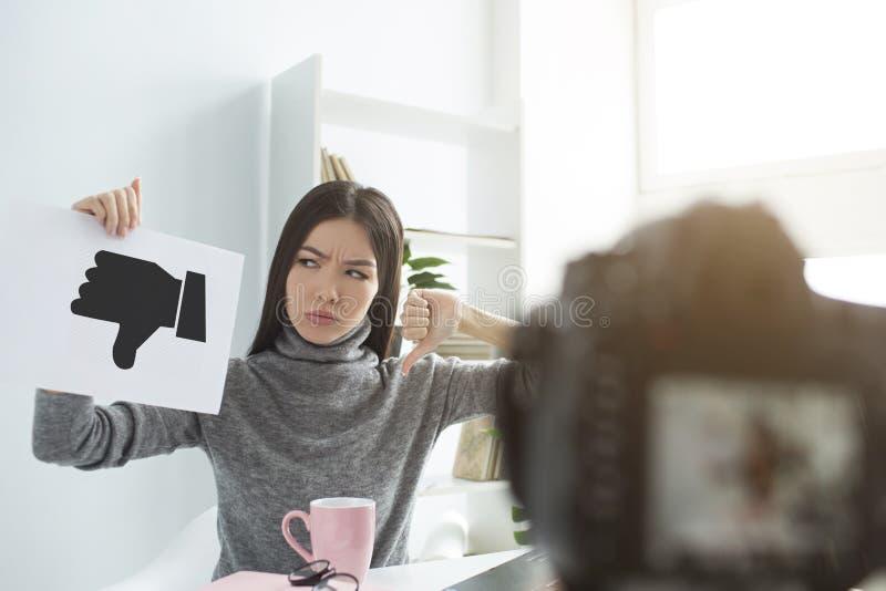 La chica joven se está sentando en la tabla delante de la cámara y está llevando a cabo un trozo de papel con la muestra de la av foto de archivo libre de regalías