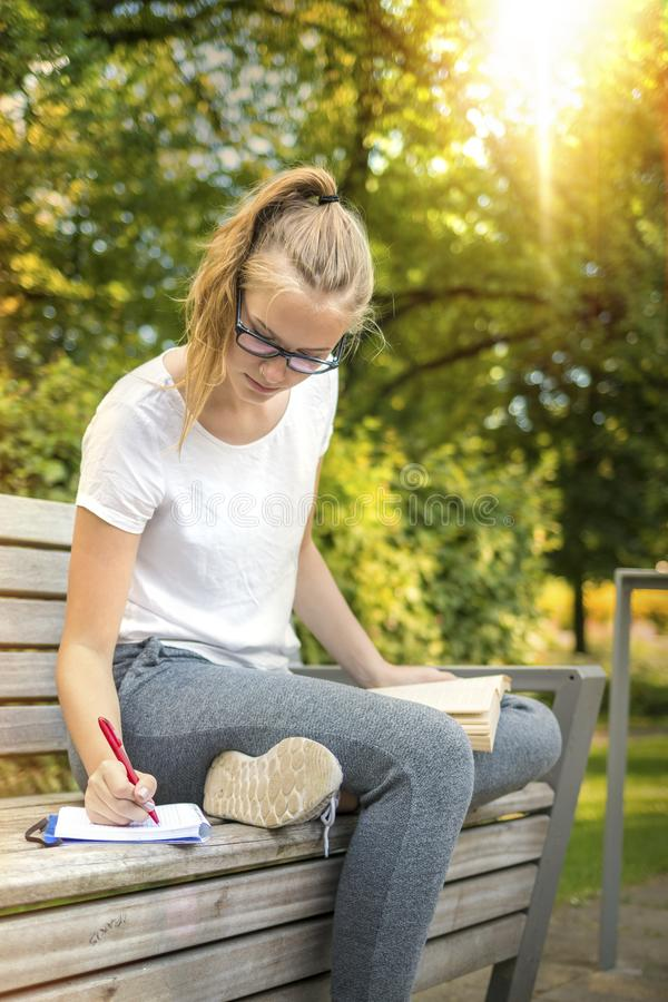 La chica joven se está sentando en un banco y está escribiendo en un libro imágenes de archivo libres de regalías