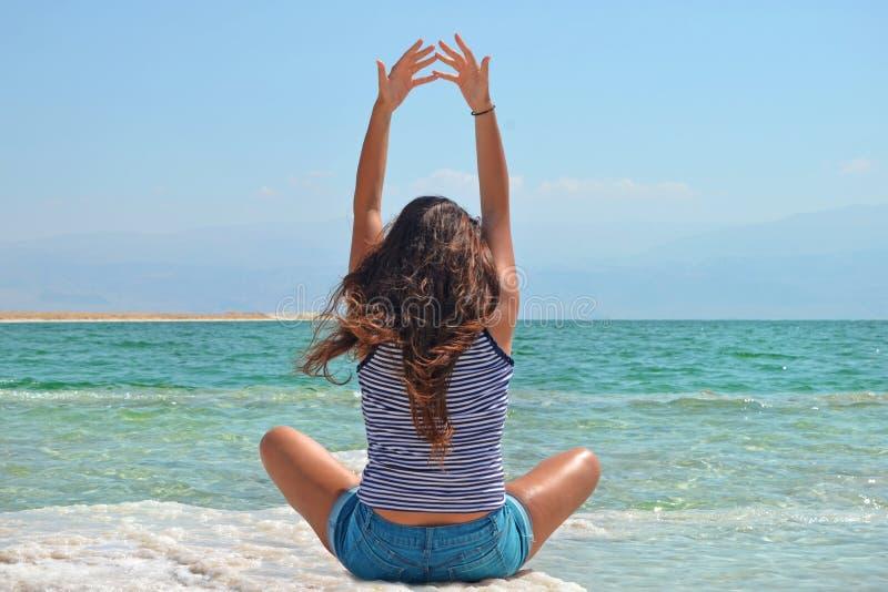 La chica joven se sienta en la orilla del mar muerto en Israel, visión desde la morenita estira sus brazos para arriba fotos de archivo libres de regalías