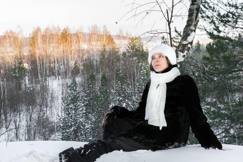 La chica joven soñadora está localizando en nieve en bosque soleado de la tarde del invierno y está mirando para arriba foto de archivo libre de regalías