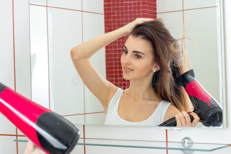 La chica joven sonriente el cabello seco delante de un espejo imagenes de archivo