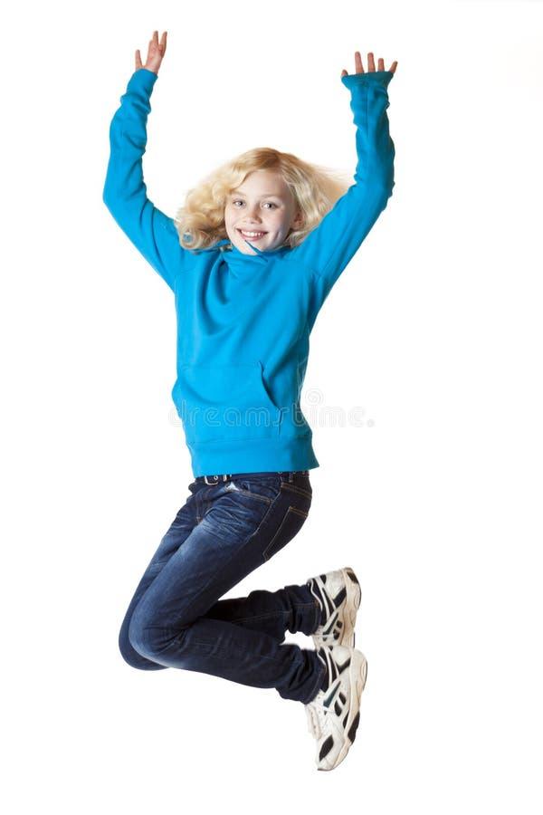 La chica joven sonriente feliz salta en el aire fotografía de archivo libre de regalías