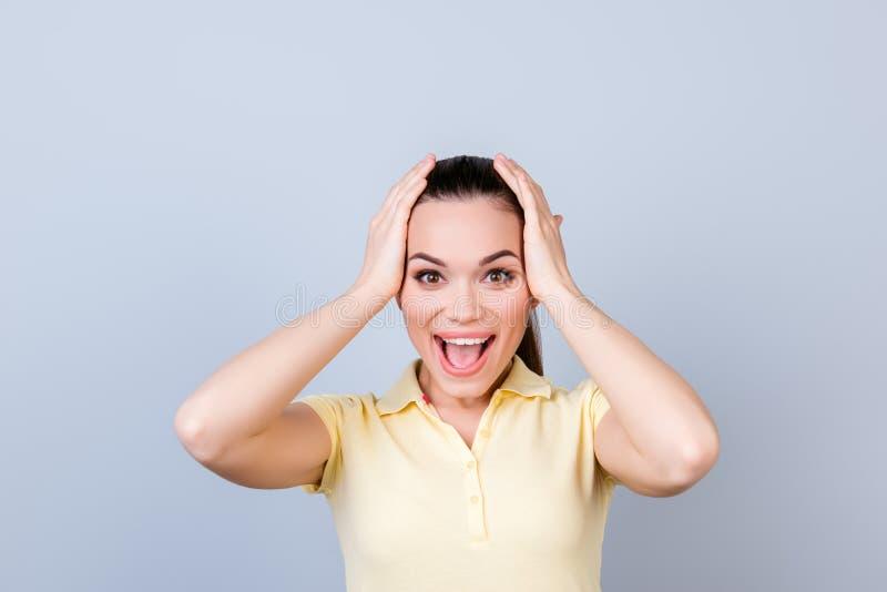 La chica joven sorprendente feliz está llevando a cabo su cabeza Ella es emocionada y fotos de archivo libres de regalías