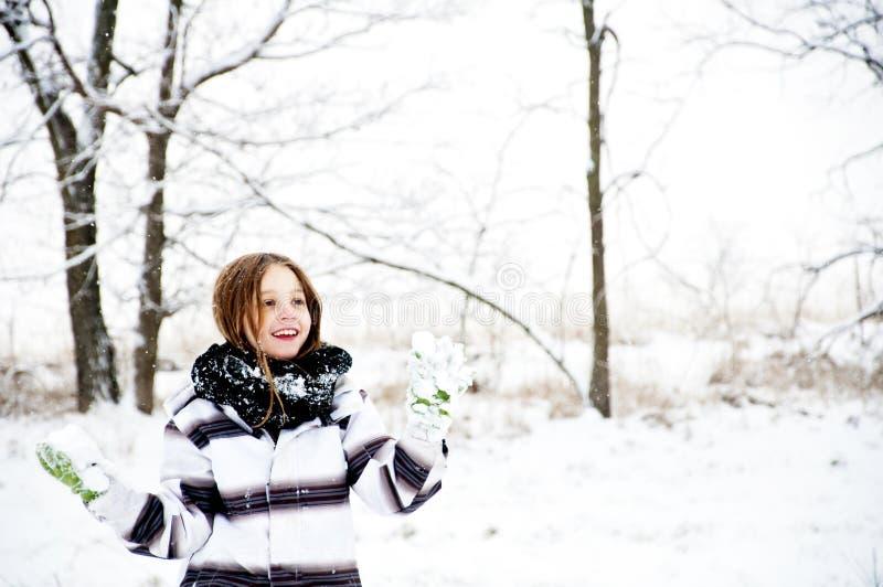 La chica joven sostiene bolas de nieve en paisaje del invierno imágenes de archivo libres de regalías