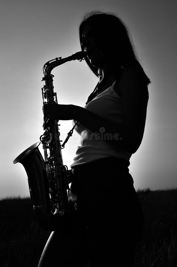 La chica joven toca el saxofón en la naturaleza fotografía de archivo