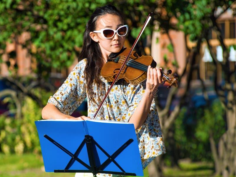 La chica joven toca el violín imagenes de archivo