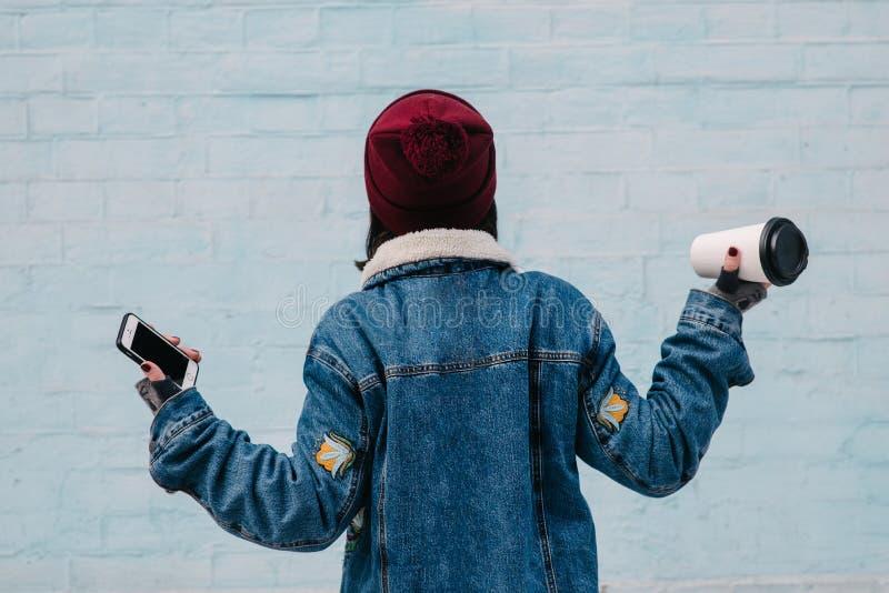 La chica joven trasera del inconformista está sosteniendo un café y un teléfono fotos de archivo libres de regalías