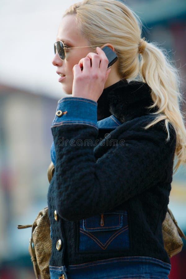 La chica joven triste habla por el móvil fotografía de archivo libre de regalías