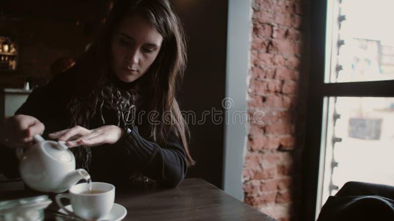 La chica joven vierte té de una caldera en una taza que se sienta en café moderno fotografía de archivo