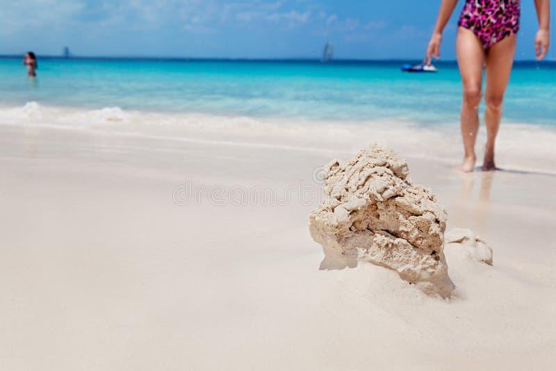 La chica joven vuelve al castillo de arena que desmenuza foto de archivo