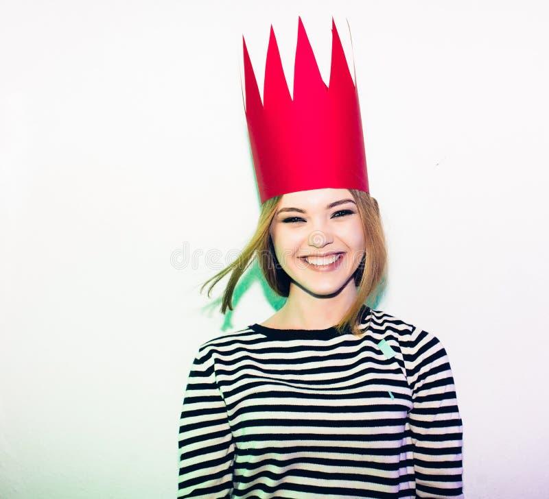 La chica marchosa en proyectores coloridos y el confeti que sonríen en el fondo blanco que celebran evento brightful, lleva pelad foto de archivo