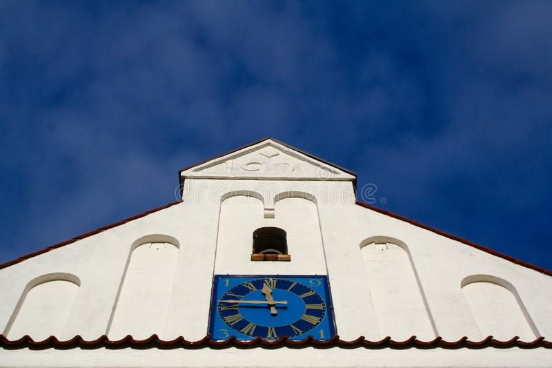 La chiesa bianca incontra il cielo blu nel Jutland, Danimarca immagini stock