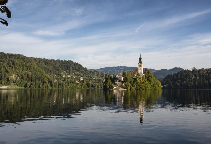 La chiesa dell'assunzione di Maria nell'isola del lago Bled, Slovenia, con riflette nell'acqua fotografia stock libera da diritti