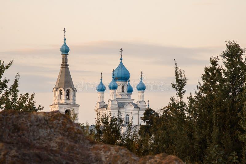 La chiesa della bianco-pietra con il blu copre con una cupola il ehind la roccia contro il cielo di sera fotografia stock