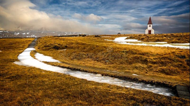 La chiesa islandese d'annata sta nel mezzo del prato di alti gras fotografie stock libere da diritti