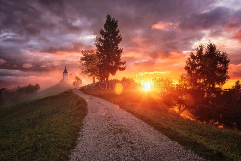 La chiesa Jamnik San Primus e Felicista all'alba, Slovenia, paesaggi incredibili, tramonto drammatico immagini stock libere da diritti