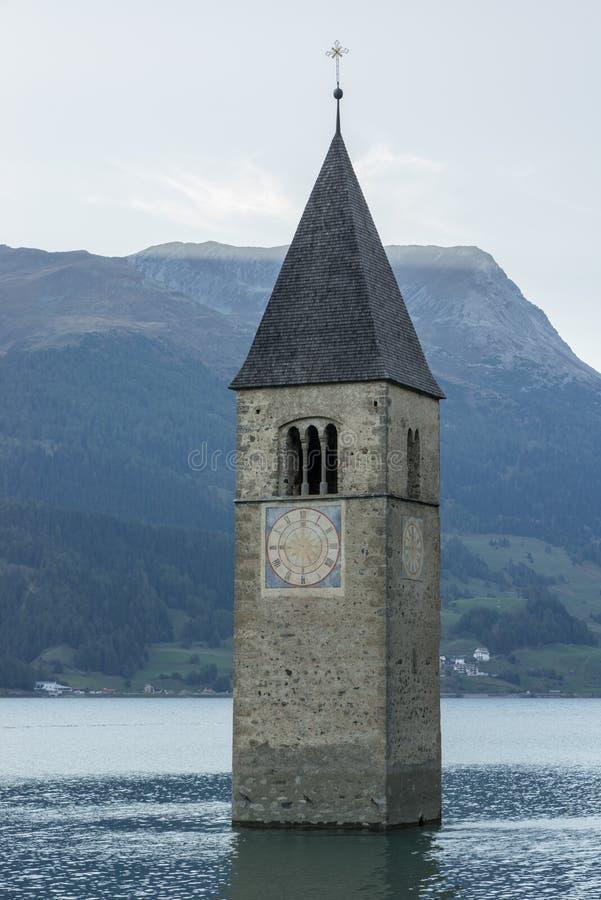 La chiesa sotto l'acqua, villaggio annegato, montagne abbellisce e picchi nel fondo Lago Reschen Lago di Resia Reschensee fotografia stock