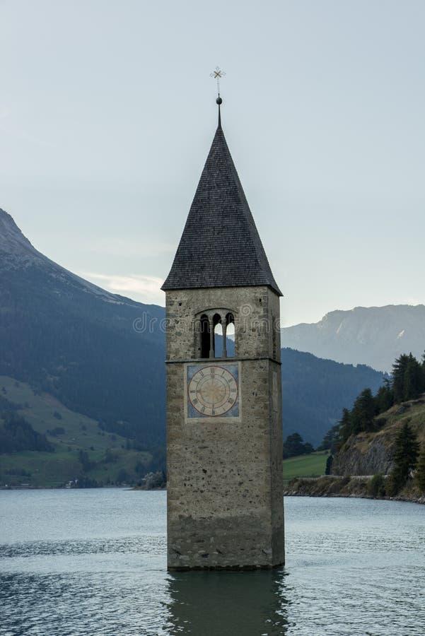 La chiesa sotto l'acqua, villaggio annegato, montagne abbellisce e picchi nel fondo Lago Reschen Lago di Resia Reschensee immagini stock libere da diritti