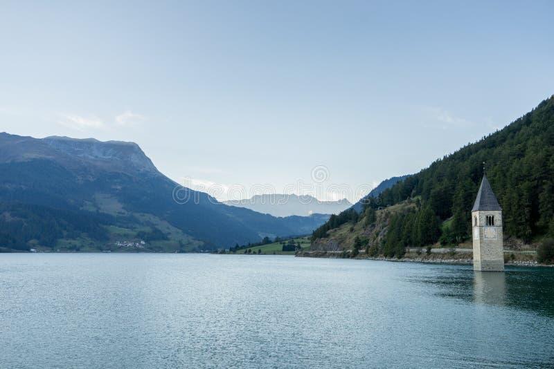 La chiesa sotto l'acqua, villaggio annegato, montagne abbellisce e picchi nel fondo Lago Reschen Lago di Resia Reschensee fotografia stock libera da diritti