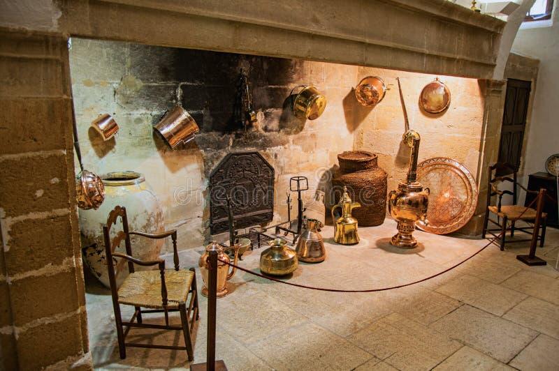 La chimenea de piedra grande con artículos de cocina de cobre decorativo y las sillas en Lourmarin se escudan foto de archivo libre de regalías