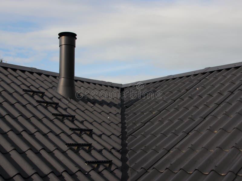 La chimenea del metal en el tejado de la placa con asegura pasos del barrendero fotografía de archivo libre de regalías