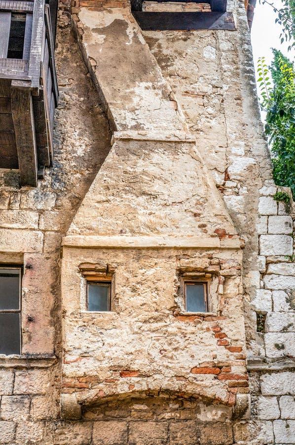 La chimenea falsa original en la pared de una casa Modelo decorativo Decoración de una pared de piedra con Windows bajo la forma  imagen de archivo