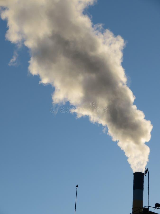 La chimenea que lanzaba una gran cantidad de humo perdió en la atmósfera imagen de archivo libre de regalías