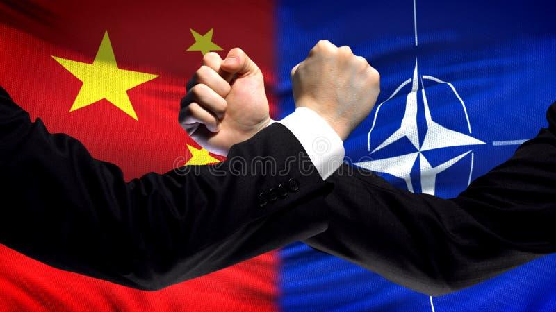 La Chine contre la confrontation de l'OTAN, désaccord de pays, poings sur le fond de drapeau photo libre de droits