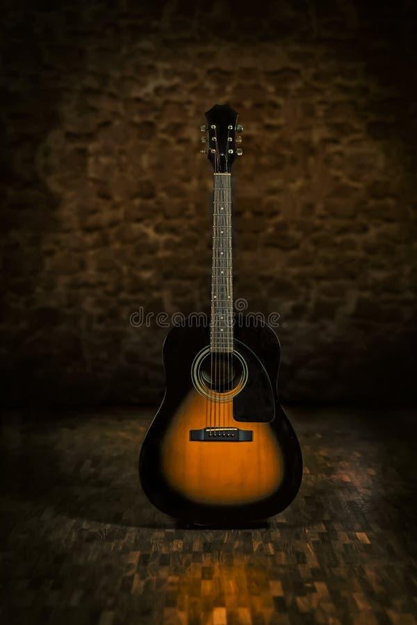 La chitarra acustica nel retro ambiente con mette il bastone tra le ruote e f di legno fotografia stock