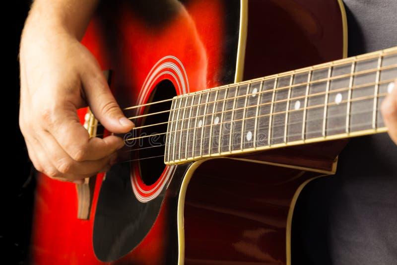 La chitarra acustica rossa, fondo scuro, si siede il musicista che gioca sullo Spagnolo classico, gioco musicale della scuola per fotografie stock libere da diritti