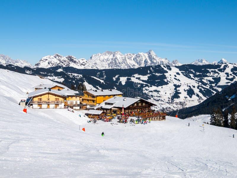 La choza en declive de la montaña del esquí de la cuesta y de los apres con la terraza del restaurante en el invierno de Saalbach imagen de archivo libre de regalías