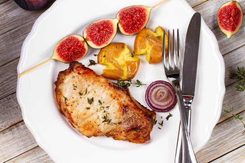 La chuleta de cerdo asada a la parrilla con los higos en Scewer, patata a la inglesa asó las patatas y el tomillo Visión desde ar foto de archivo