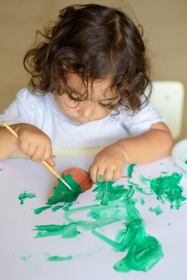 La chute adorable de peinture d'enfant part à la table photographie stock libre de droits