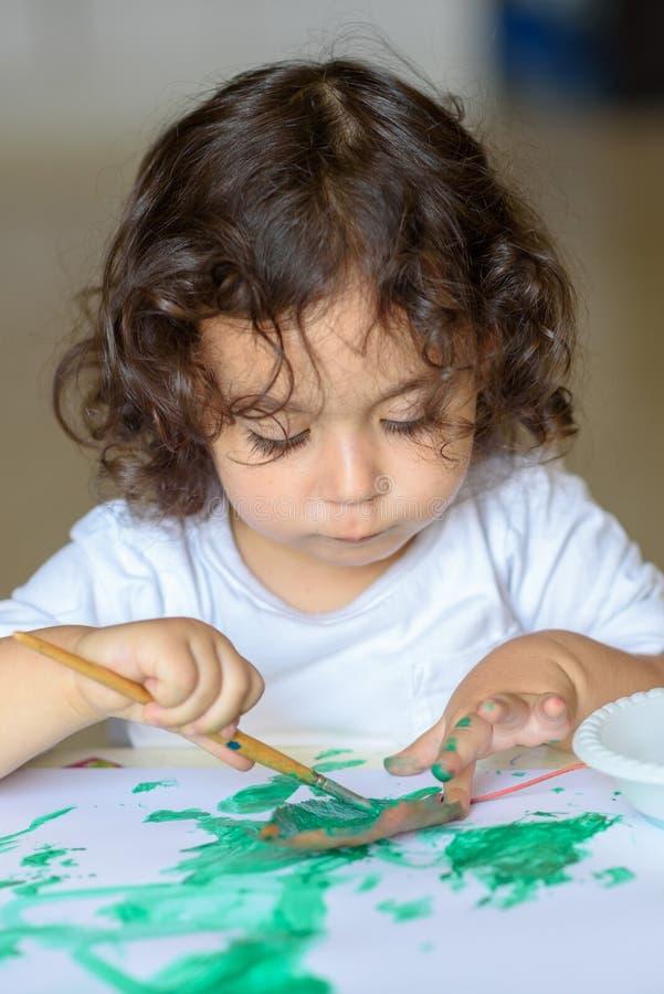 La chute adorable de peinture d'enfant part à la table photos stock