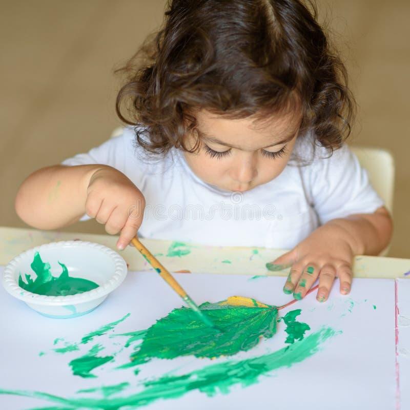 La chute adorable de peinture d'enfant part à la table image stock