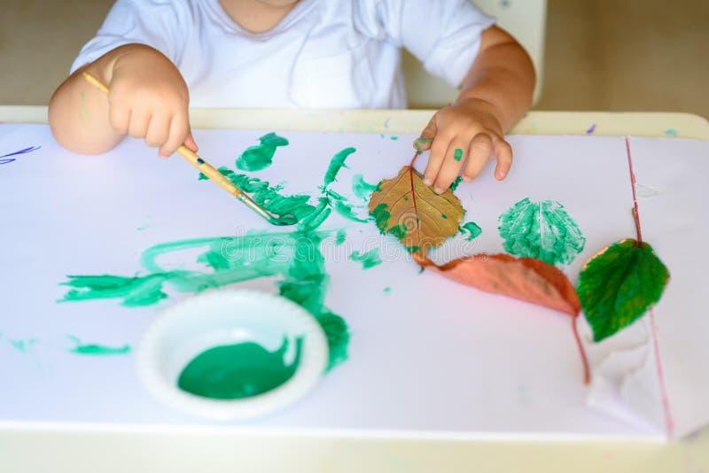 La chute adorable de peinture d'enfant part à la table images libres de droits