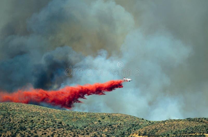 La chute blanche d'avions ignifuge en tant qu'elle lutte le feu de forêt faisant rage image stock