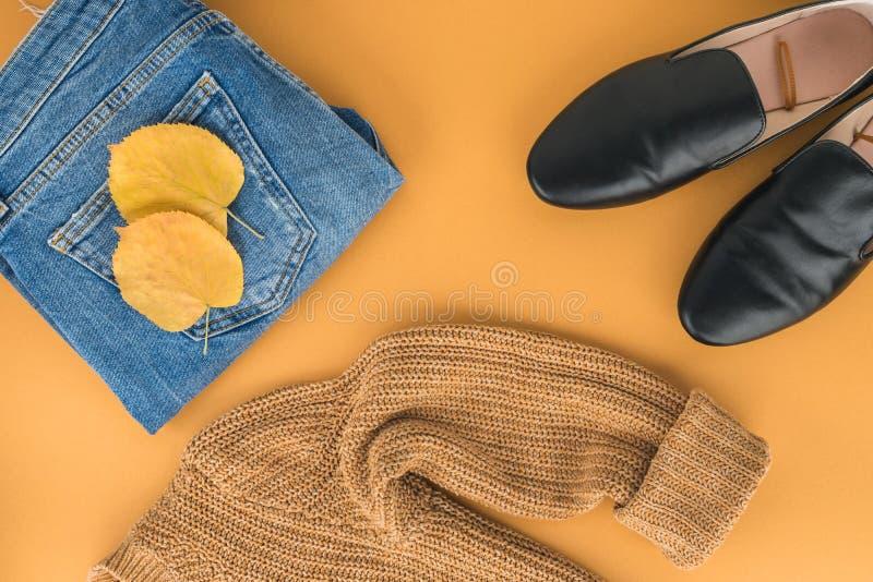 La chute/hiver de femme vêtx la pose sur le fond jaune Les jeans, jaunissent le pullover tricoté, chaussures plates noires photographie stock libre de droits