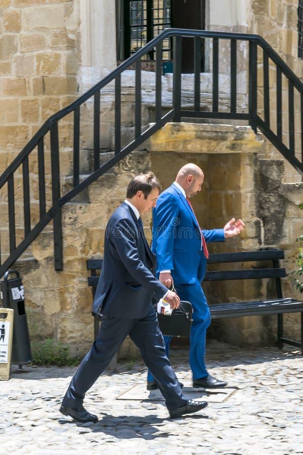 LA CHYPRE, NICOSIE - 10 JUIN 2019 : Deux hommes d'affaires habillés dans les costumes bleus marchant rapidement ou se dépêchant p photographie stock